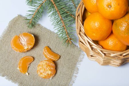 Tangerines in a wicker basket. Next to the basket is peeled mandarin on a piece of linen. Visible slices of tangerine and a branch of blue spruce. On white background.