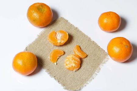 Mandarins are laid out on a white surface. Next to them is peeled mandarin on a piece of linen. Visible slices of mandarin. On white background.