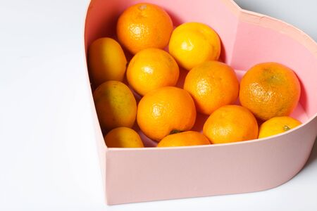 Tangerines are stacked in a container in the shape of a heart. On white background.