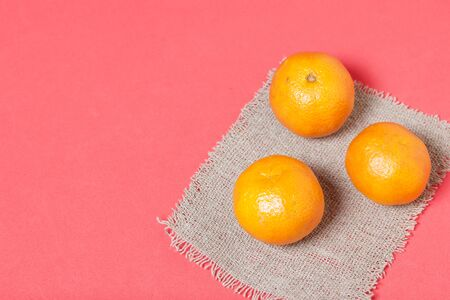 Tangerines are folded on linen. On a coral background.