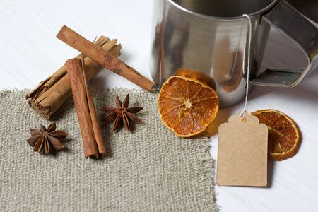 Tea bag in a steel mug. Anise, cinnamon sticks and slices of dried tangerines. Lying on a piece of linen. Against the background of white painted boards.