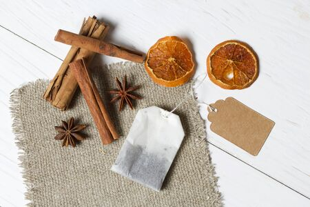 A bag of tea, anise, cinnamon sticks and slices of dried tangerines. Lying on a piece of linen. Against the background of white painted boards. Stock Photo