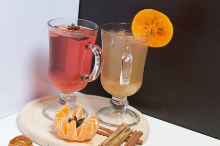 Drink red and yellow in glass goblets. Anise stars, a slice of persimmon float in it. Next to the linen fabric is peeled mandarin, dried mandarin rings, cinnamon sticks and anise stars. Stock Photo