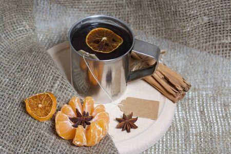 Brewed tea bag in a metal mug. A slice of dried mandarin floats in it. Nearby peeled mandarin, anise stars and cinnamon sticks.