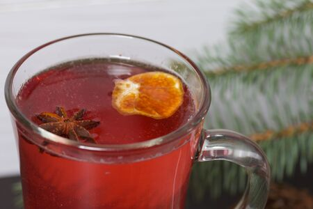 A glass of red drink stands on a piece of linen. A slice of dried orange and anise floats in it. Nearby are cinnamon sticks and dried oranges and a spruce branch. Stock Photo
