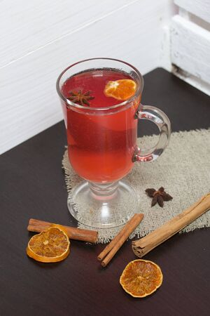 A glass of red drink stands on a piece of linen. A slice of dried orange and anise floats in it. Nearby are cinnamon sticks and dried oranges.