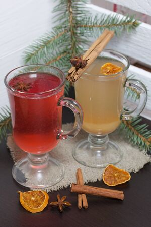 Glasses with a drink of orange and red are on a piece of linen. Slices of dried orange and anise float in them. Nearby are cinnamon sticks and dried oranges and a spruce branch. Stock Photo