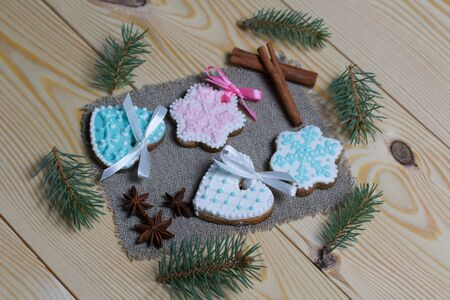 Spicy gingerbread cookie decorated with multi-colored sugar icing. Lies on pine boards. Nearby are cinnamon sticks, anise and spruce branches. Stock Photo