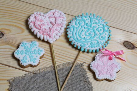 Spicy gingerbread cookie. On a stick and without it. Garnished with multicolored sugar glaze. Lies on pine boards. Stock Photo