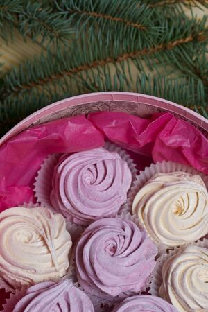 Homemade marshmallows in a round box. Decorated with fir branches. On pine boards. View from above.
