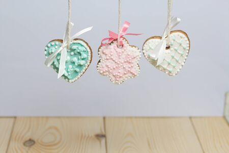 Spicy gingerbread cookie decorated with multi-colored sugar icing. Suspended on a cord. Decorated with spruce branch.