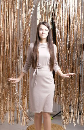 A girl in a beige dress stands among the shining rain curtain. He smiles and spreads his hands.