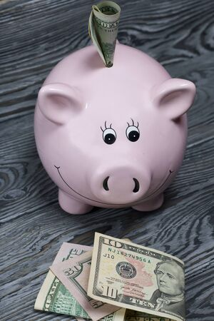 Ceramic piggy bank in the form of a pink pig. Nearby are dollar bills. One of them sticks out of the piggy bank. Against the background of aged wooden boards with a black structure. Banque d'images