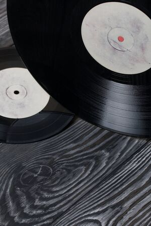 Old vinyl records. Against the background of brushed pine boards painted in black and white.