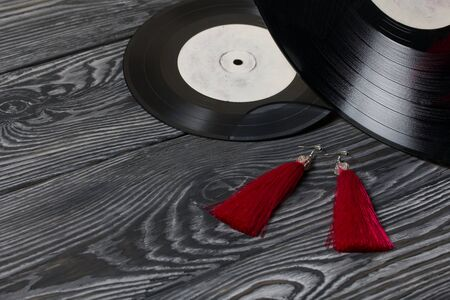 Homemade tassel earrings in red. Against the background of old vinyl records and brushed pine boards painted in black and white. Stock Photo