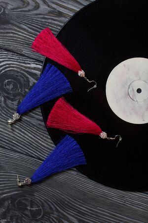 Homemade earrings tassels of red and blue. Against the background of old vinyl records and brushed pine boards painted in black and white.
