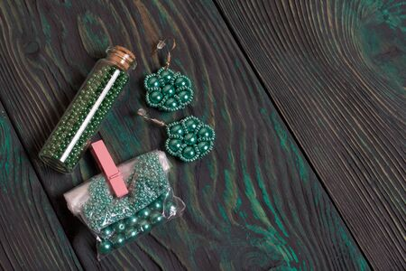 Homemade green earrings from beads. Next to the package is beads. On brushed pine boards painted in black and green.