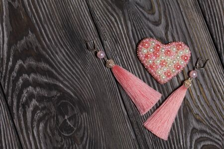 Heart bead brooch. Earrings tassels pink. On brushed pine boards painted in black and white. Archivio Fotografico