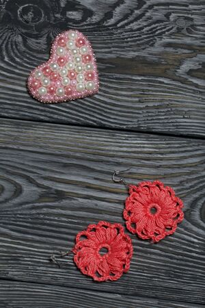 Heart bead brooch. Knitted earrings in pink. On brushed pine boards painted in black and white. Archivio Fotografico