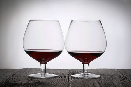 Glasses with red dry wine. Stand on wooden boards. Shot in backlight. Foto de archivo