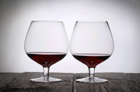 Glazen met rode droge wijn. Ga op houten planken staan. Geschoten in tegenlicht. Stockfoto