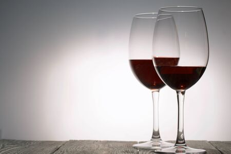 Glasses with red dry wine. Stand on wooden boards. Shot in backlight.