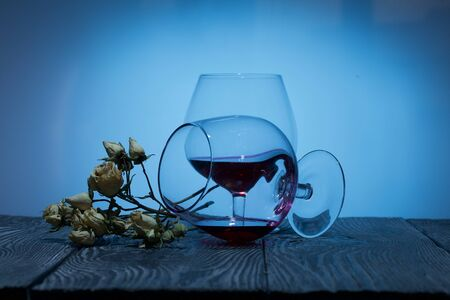 Glasses with red dry wine. One of them lies on its side with the remains of wine. Dried rose flowers. Stand on wooden boards. Shot in backlight. 스톡 콘텐츠