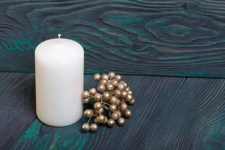 Big candle. Nearby lies a bouquet of artificial balls painted in golden color. Against the background of brushed boards painted in black and green.
