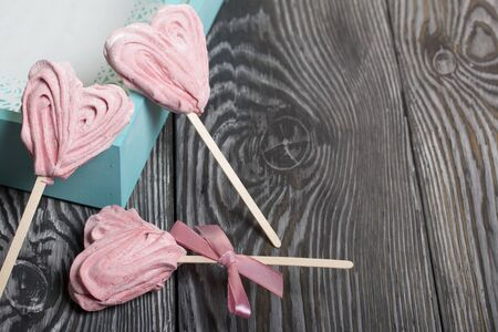 Delicate pink marshmallows in the shape of a heart on a stick. One with a ribbon tied to a bow. Near the turquoise color tray. Lies on brushed pine boards painted in black and white. Reklamní fotografie