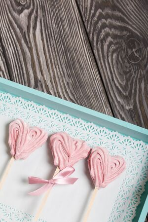 Delicate pink marshmallows in the shape of a heart on a stick. One with a ribbon tied to a bow. Lies in a tray of turquoise color. Against the background of brushed pine boards painted in black and white.