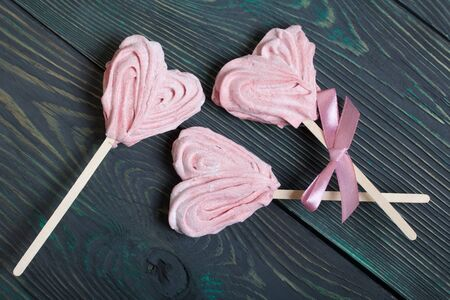 Delicate pink marshmallows in the shape of a heart on a stick. One with a ribbon tied to a bow. Lies on brushed pine boards painted in black and green.