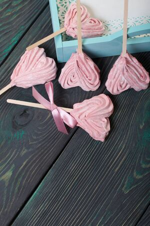 Delicate pink marshmallows in the shape of a heart on a stick. One with a ribbon tied to a bow. Near the turquoise color tray. Lies on brushed pine boards painted in black and green.