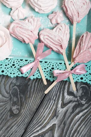 Delicate pink marshmallows in the shape of a heart on a stick. Some with a ribbon tied to a bow. Lies on a turquoise tray. Against the background of brushed pine boards painted in black and green.