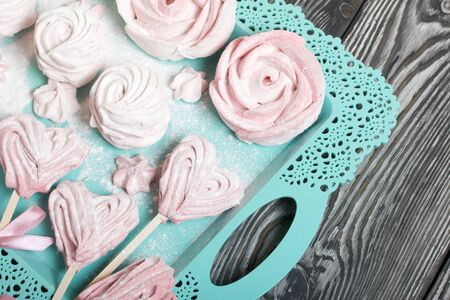 Delicate pink marshmallows in the shape of a heart on a stick. Some with a ribbon tied to a bow. Lies on a turquoise tray. Against the background of brushed pine boards painted in black and white.