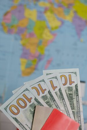 Hundred dollar banknotes. Bank cards. Against the background of a world map. Silhouettes of continents are visible on it.