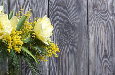 Bouquet of yellow tulips and mimosa. Against the background of brushed boards.