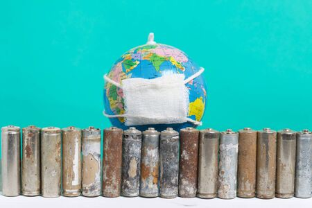 Spent finger-type batteries coated with corrosion. Stand in a row. Globe with gauze bandage. Environmental protection, Earth Day. On a green background.