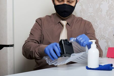 Parcel delivery during self-isolation. A man in rubber gloves and a mask pulls out a camera of their bubble packaging from the parcel. Visible spray with a disinfectant and a napkin.