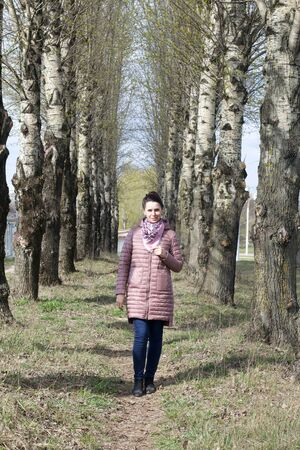 A girl walks along a spring poplar alley. It goes between two rows of tall trees. Dressed in a spring jacket, a scarf around her neck. Around the blossoming greens on the trees. 版權商用圖片
