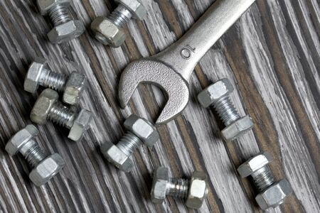 A handful of metal bolts with screwed nuts. Nearby a wrench. They lie on pine brushing boards painted black. World Labor Day. Stock Photo