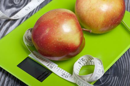 Apples and a measuring tape lie on the scales. Scales show zero. On brushed pine boards. Symbol of World No Diet Day.