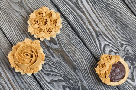 Chocolate ganache tartlets and cakes. Decorated with oil cream flowers. The cream has a caramel color. On brushed pine boards painted black.