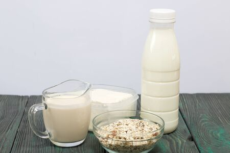 Bottle and glass with milk. Next to granola and soft cheese in a container. On brushed pine boards.