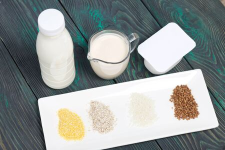 Bottle and glass with milk. Near the cottage cheese and a container with cereals: buckwheat, rice, barley and corn. On brushed pine boards.