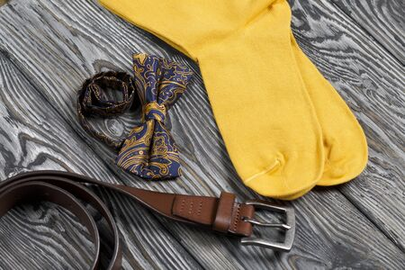 Accessories, belt, bow-tie and yellow socks. Shot from above, on brushed pine boards.