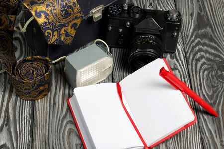 Photographer accessories. Camera, flash, tie, notebook and pen. On brushed pine boards. 写真素材