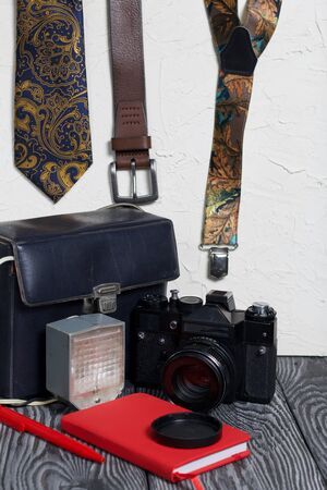 Photographer accessories. Camera and flash. Near tie, belt, suspenders, notebook and pen. On brushed pine boards.