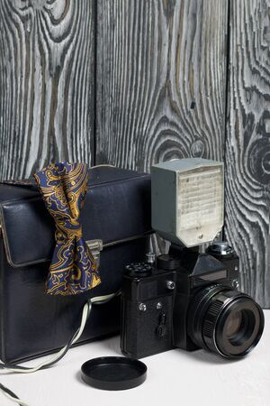 Photographer accessories. Camera and flash. There is a bow tie on the camera. Against the background of brushed pine boards.