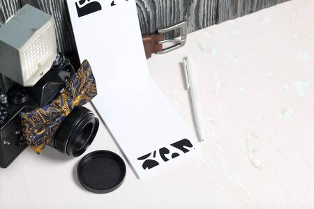 Photographer accessories. Camera and flash. Nearby is a bow tie, belt and notebook with pen. Against the background of brushed pine boards. 写真素材
