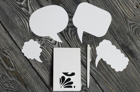 Speech bubbles on a background of brushed pine boards. Blogger notes pad and pen.